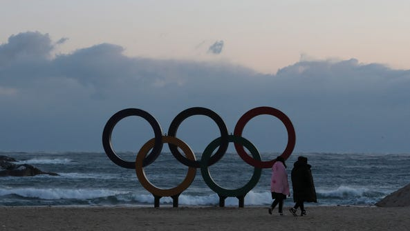 Visitors walk near the Olympic Rings set up on a beach