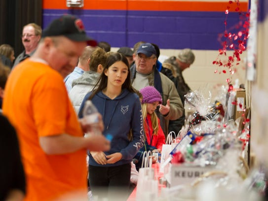 People browse the silent auction table during a fundraiser
