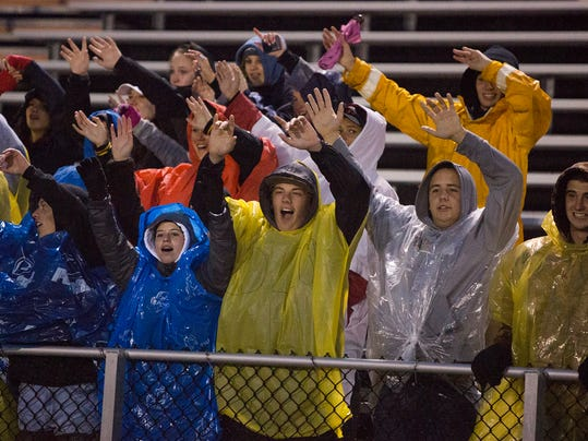A small Red Lion student section dons rain gear during the Oct. 2 game against Northeastern. It was one of several games played as scheduled in Week 5 despite heavy rain. In deciding whether to play or postpone, schools consider multiple factors, including player safety and field conditions.