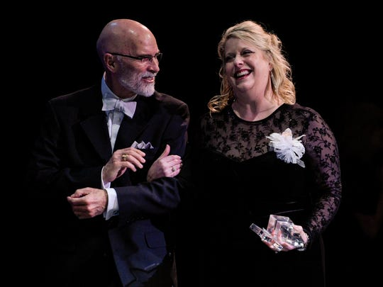 Milissa Welch, an American Sign Language Interpreter at Lafayette High School, is escorted by Bruce Conques after receiving the Inspirational Award during the Lafayette Education Foundation Teacher Awards on Thursday.