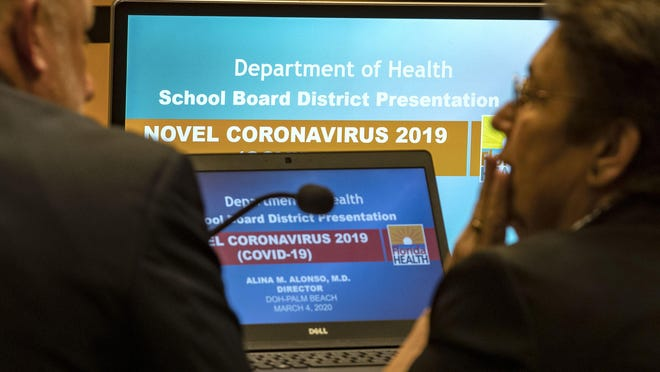 Dr. Alina Alonso, (right) Florida Department of Health in Palm Beach County Director talks with Paul Strauss, Palm Beach County School District Director of Environmental and Conservation Services, before presentation to the Palm Beach County School Board about the coronavirus in West Palm Beach, March 4, 2020.