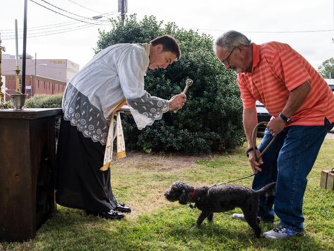 Father Lawrence Holcombe blesses Bella the dog for