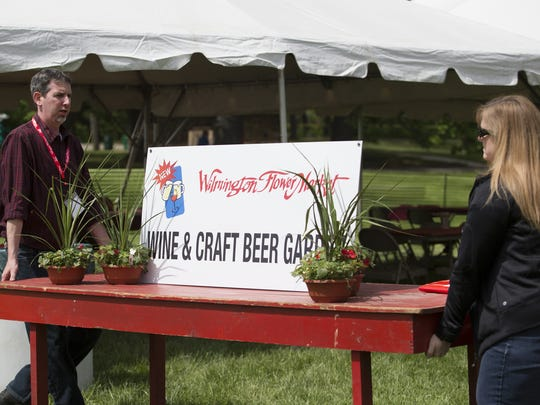 Jimmy Malick and his wife Amy work to set up the new Wilmington Flower Market beer garden at Rockford Park on Wednesday.