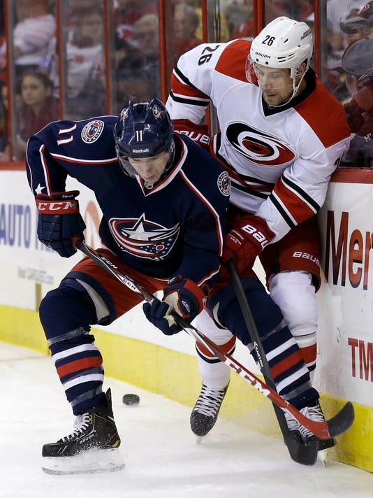 Carolina Hurricanes' John-Michael Liles (26) and Columbus Blue Jackets' Matt Calvert (11) skate for possession of the puck during the first period of an NHL hockey game in Raleigh, N.C., Saturday, March 29, 2014. (AP Photo/Gerry Broome)