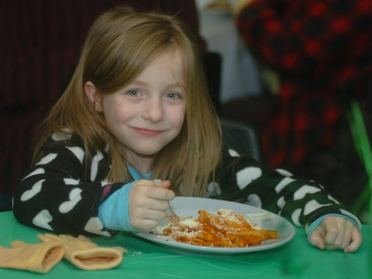 Claire Spilker, 6, from Royal Oak, is all smiles as she enjoys a plate full of mostaccioli at the St. Patrick's Day Parade fundraiser at the VFW in Royal Oak.