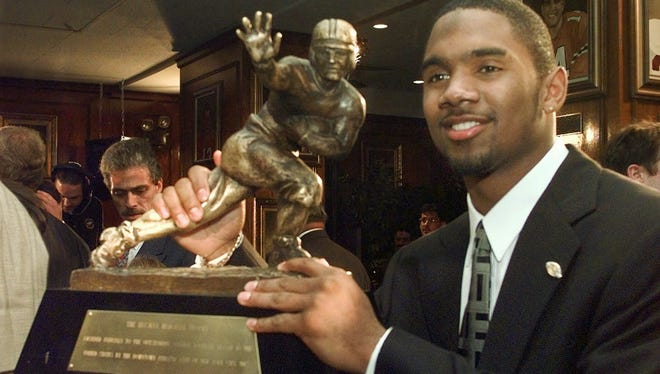 Michigan's Charles Woodson holds the Heisman Trophy after winning the award on Dec. 13, 1997.Univeristy of Tennessee quarterback Peyton Manning finished second in the voting.