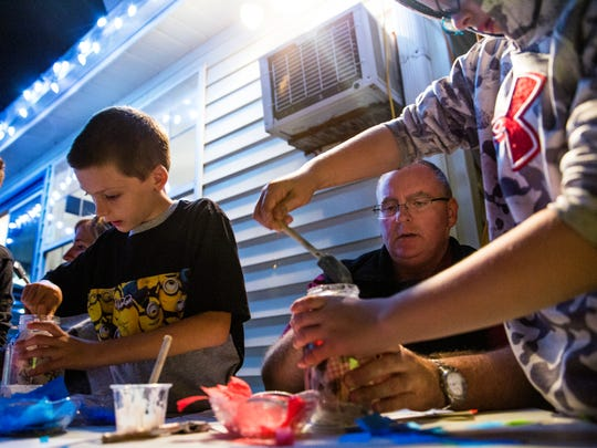 Shon Wells, center, helps his sons Caleb, 9, right, and Noah, 8, with their holiday candle jars in memory of their mother, Janet Wells, during a family support group meeting at Valerie's House in Fort Myers on Monday, Dec. 11, 2017. Janet died of colon cancer in June.