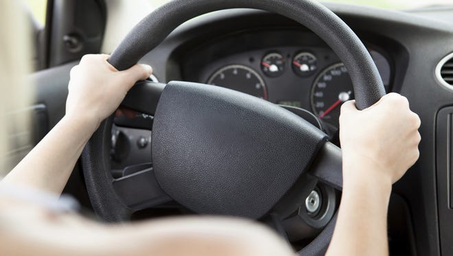 Woman holding sternly to a steering wheel.