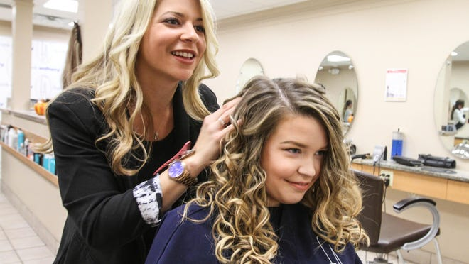Stylist Brianna Iapalucci finishes up Brenna Burke's beach waves with hair extensions at Frank Anthony Salon.