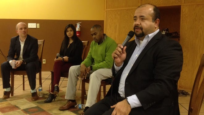 Rev. Greg Diaz addresses the audience at an immigration forum at Las Americas after-school center in Hickory Hill Thursday night. With him are (from left) Latino Memphis leader Mauricio Calvo, high school student Chantel Barcenas and Rev. Derrick Anderson.