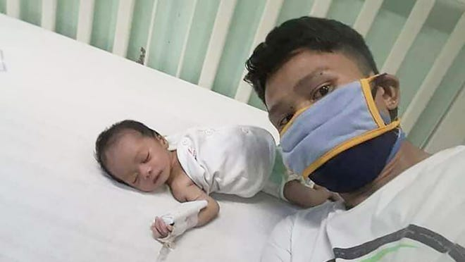 In this handout photo provided by Ronnel Manjares, Ronnel takes a selfie with his son Kobe at a hospital in metropolitan Manila, Philippines Saturday April 18, 2020. Kobe was heralded in the Philippines as the country's youngest COVID-19 survivor, a baby who'd become infected with and conquered the coronavirus during his first 16 days of life. To Ronnel Manjares and Trisha May Noche, he was Kobe Christ, their second child.