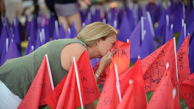 On the lawn of the First Congregational Church Friday evening, Theresa Reddish, of Natick, kisses a flag in memory of her son, Michael Reddish, who died in 2017 of a fentanyl overdose. Purple flags were placed on the church lawn in advance of Opioid Awareness Day August 31. There were 2, 015 opioid overdose deaths in Massachusetts in 2019.