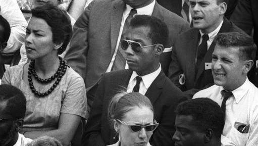 """This image released by Magnolia Pictures shows James Baldwin, center, in """"I Am Not Your Negro."""" In Raoul Peck's Oscar-nominated documentary, Baldwin's searing observations on race and America are resurrected for today. Peck and others say Baldwin's words could hardly be more urgent."""