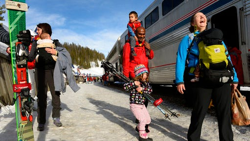 FILE - In this March 15, 2015, file photo, Val Hovland, right, laughs as young Emily Griffin, 4, says all the poles she tries to carry are too heavy, as they head towards Winter Park after riding the Amtrak Winter Park Resort Ski Train at Winter Park, Colo. Behind them are Hovland's husband Ram Sreerangam with young Kavi Hovland, 2, on his shoulders.  Amtrak and the resort announced Wednesday, March 22, 2017, that they are going to keep the train running for the foreseeable future and may possibly expand service.