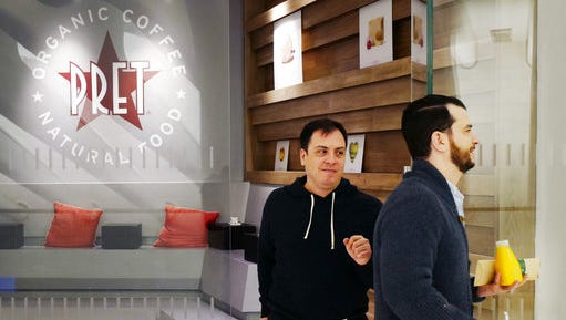 Customers step out of a Pret a Manger sandwich shop, Friday, April 14, 2017 in New York. Pret says its two vegetarian-only shops sell far more desserts than its other stores, a quirk it says may indicate that people want to treat themselves more after they feel they've had a healthy meal.
