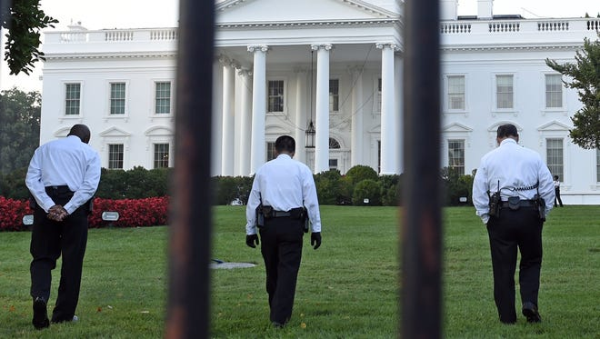 Uniformed Secret Service officers walk along the lawn on the North side of the White House in Washington, Saturday, Sept. 20, 2014.