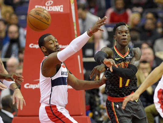 Atlanta Hawks guard Dennis Schroder (17), of Germany, passes the ball past Washington Wizards guard John Wall (2) during the first half of an NBA basketball game, Saturday, Nov. 11, 2017, in Washington. (AP Photo/Nick Wass)