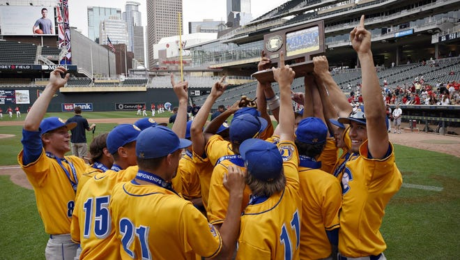 Cathedral players hold up the trophy for the fans after beating Minnehaha Academy for the Class 2A championship title Monday at Target Field. Cathedral beat Minnehaha Academy 10-1.