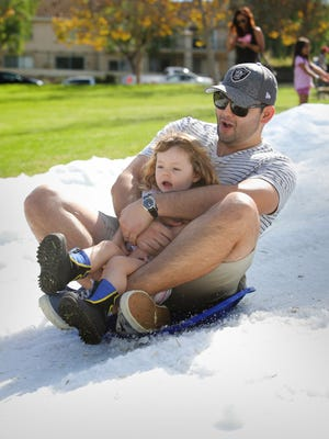James Landeros, of Santa Barbara, holds onto his daughter, Kalissa, 2, as they slide down the snow slide at Rancho Simi Recreation and Park District's eight annual Snowfest held this weekend at Rancho Madera Community Park in Simi Valley.