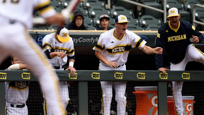 The Michigan bench celebrates as Jake Bivens (18) walks with the bases loaded against Maryland relief pitcher Robert Galligan during the fourth inning of the NCAA Big Ten tournament championship college baseball game Sunday, May 24, 2015, in Minneapolis.