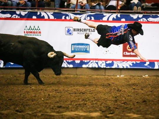 A bull fighter is thrown in the air by a bull during the Cinch Chute-Out Saturday, Feb. 17, 2018, at Foster Communications Coliseum.