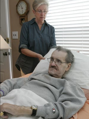 Kathie Browning adjusts her husband's pillow at their Toms River home. Medicare has denied their claims for ambulance service to take him to medical treatment for his leg wounds.