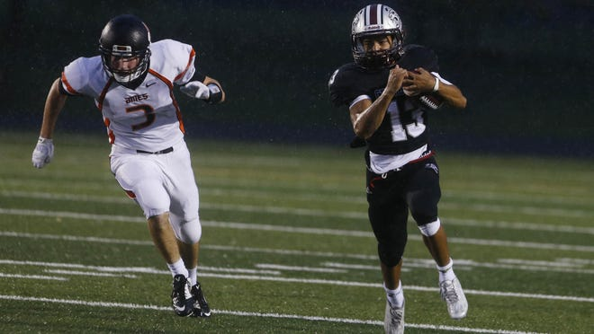 Ankeny Centennial's Ryan VanBaale, right, breaks away from Ames' Logan Wallen on Friday in Ankeny. VanBaale had 190 yards rushing and two touchdowns.