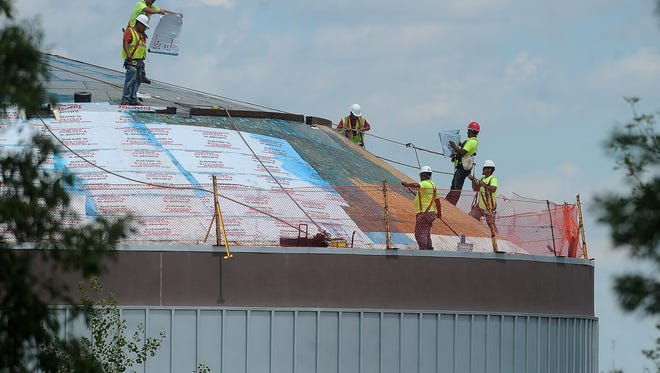 Architectural Roofing and Sheetmetal employees work to replace the Wells Fargo CineDome roof at the Washington Pavilion in 2014.