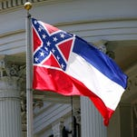 In this June 23, 2015, file photograph, the state flag of Mississippi is unfurled against the front of the Governor's Mansion in Jackson, Miss.