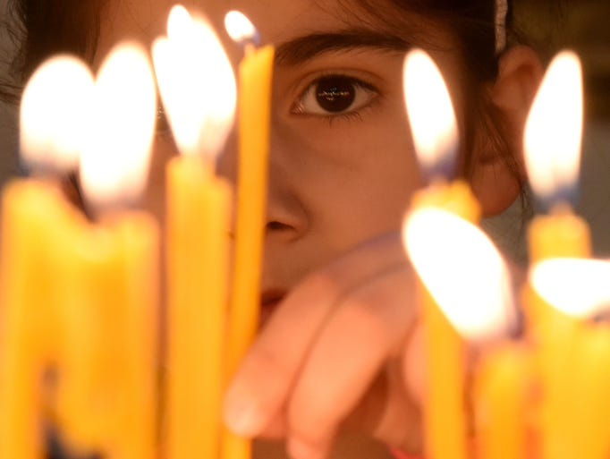 A girl places a candle during a religious service at
