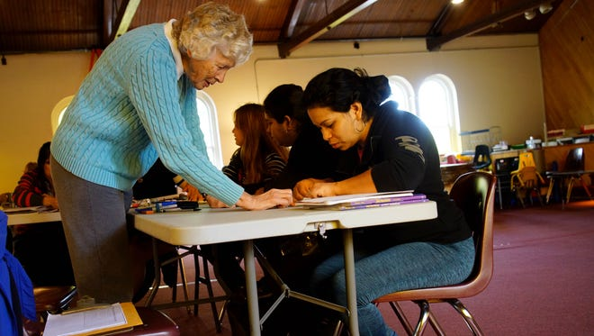 Janet Saunders, a volunteer for Literacy Delaware, works on an English language exercise with Maria Rivera.