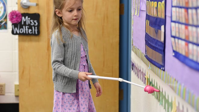 Isla Waldron points out the numbers as the class counts by fives in Megan Wolfelt's full-day kindergarten class at Riffenburgh Elementary on Monday, March 28, 2016.