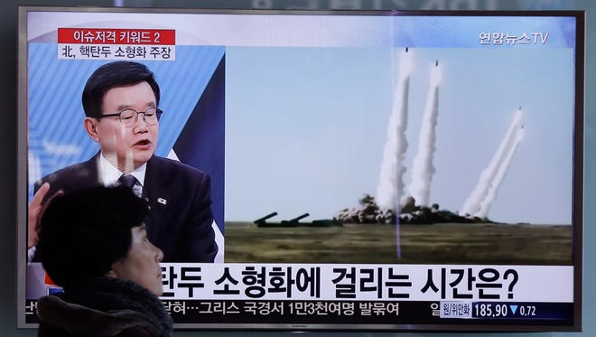 """A woman passes by a TV screen showing a file footage of the missile launch conducted by North Korea, at Seoul Railway Station in Seoul, South Korea, Thursday, March 10, 2016. North Korea fired two short-range ballistic missiles into the sea on Thursday, South Korea's military said, a likely show of anger at continuing springtime war games by rivals Washington and Seoul and another ratcheting up of hostility on the already anxious Korean Peninsula. The screen reads """"North Korea's nuclear warheads."""""""