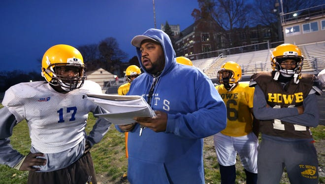 Second-year Howe High School head football coach Craig Chambers outlines a play for senior quarterback Chris Mundy, left, during practice at the school at 4900 Julian Ave., Indianapolis, on Wednesday, Nov. 5, 2014. After their 20-13 win over the South Decatur Cougars, the Hornets advance to their first sectional championship football game in school history.