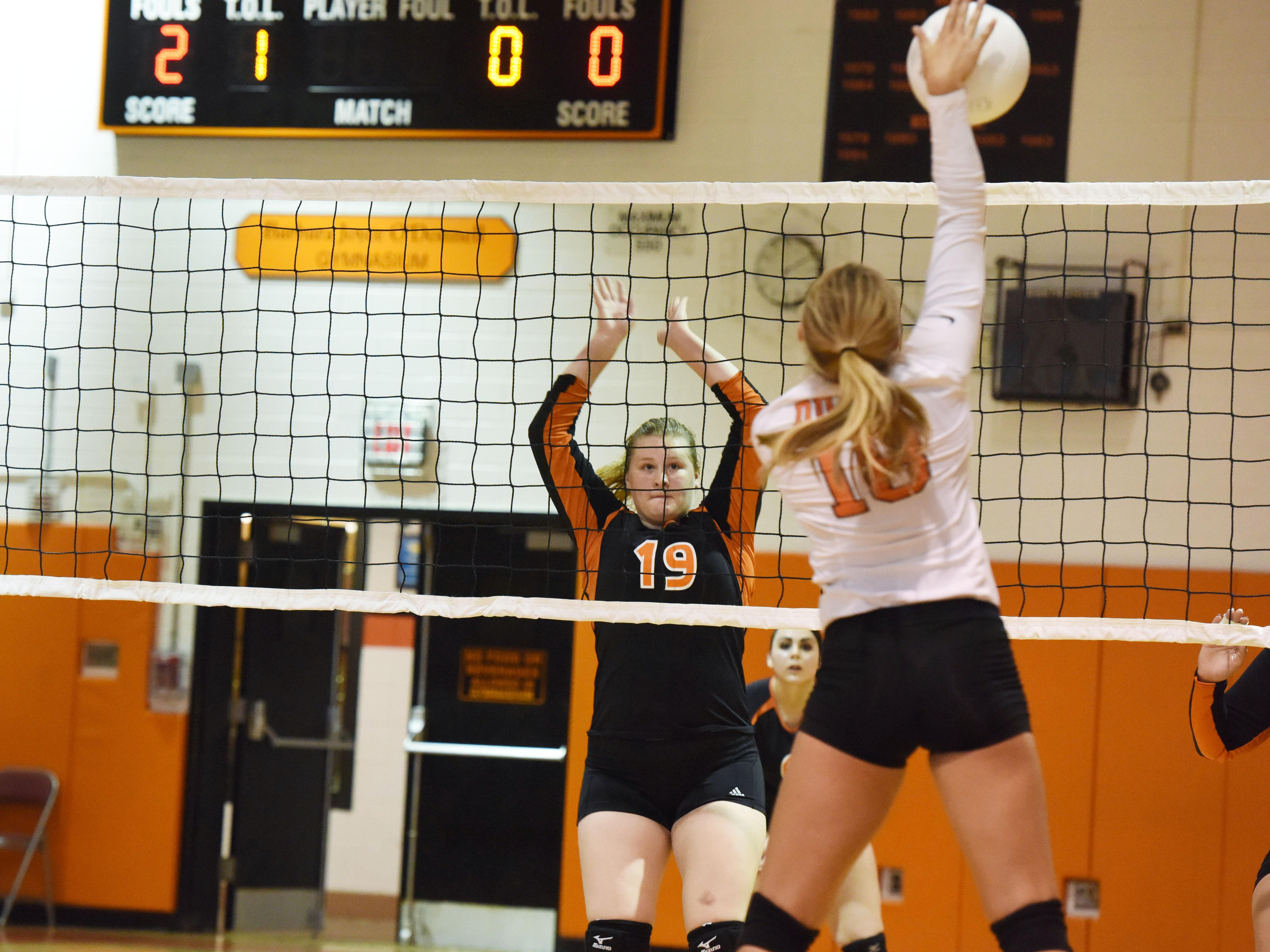 Dover's Brianna Swart, left, goes to block a spike from Marlboro's Amber Mianti, right.