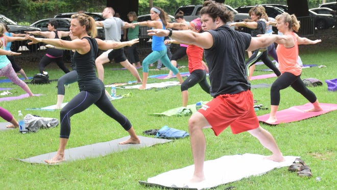 Central Louisiana residents join with thousands of others around the world to practice yoga at the Big Island near Bringhurst Field on International Yoga Day in 2015.
