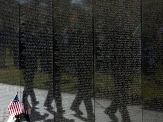 United States Park Police honor guards are reflected in the Vietnam Veterans Wall Memorial as they march during a ceremony in commemoration of Veterans Day, Tuesday in Washington. Americans marked Veterans Day on Tuesday with parades, speeches and military discounts, while in Europe the holiday known as Armistice Day held special meaning in the centennial year of the start of World War I.