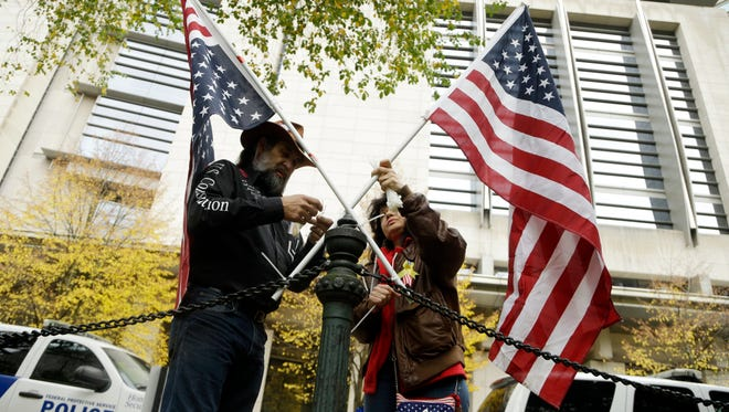 Maureen Valdez, right, and David Brugger attach crossed American flags to a rail post outside the federal courthouse in Portland, Ore., Tuesday, Oct. 25, 2016. A handful of supporters have gathered outside the courthouse as a jury continues to deliberate on the fate of seven defendants involved with the armed occupation of a national wildlife refuge in central Oregon earlier this year.