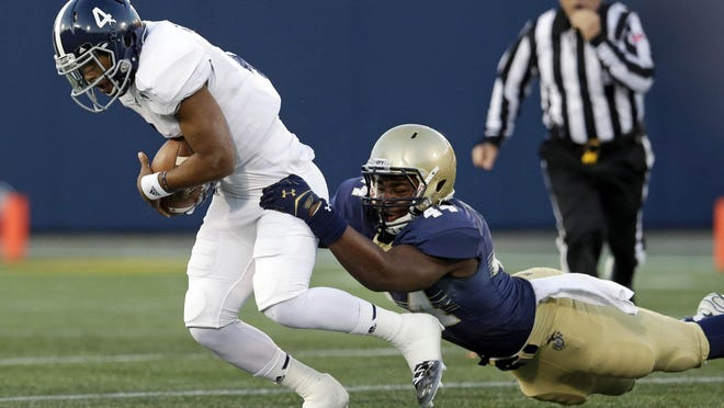 Georgia Southern quarterback Kevin Ellison, left, is tackled during a 2014 game against Navy.