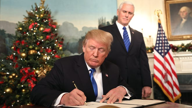 Vice President Pence watches as President Trump sign his proclamation about his decision to recognize Jerusalem as the capital of Israel, and his plan to relocate the U.S. Embassy to that city, in the Diplomatic Room of the White House in Washington, on Dec. 6, 2017.