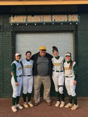 Longtime Crest High athletics supporter Larry McEntire takes a photo with Charger softball players in front of the pressbox named in his honor.