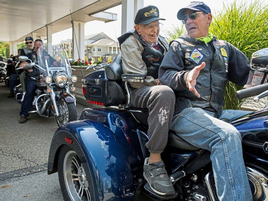 Alvin Graf, 98, talks with Art Terracio, of Lawrence County, Pa., before riding around the block at the Lutheran Senior Life Passavant Community in Zelienople, Pa., Sunday, Sept. 10, 2017. Caretakers at the Community wanted to fulfill Graf's wish to ride a motorcycle after not having ridden one since WWII. The American Legion Riders offered their help and came out to not only grant Graf's wish, but also other senior residents. (Antonella Crescimbeni/Pittsburgh Post-Gazette via AP)