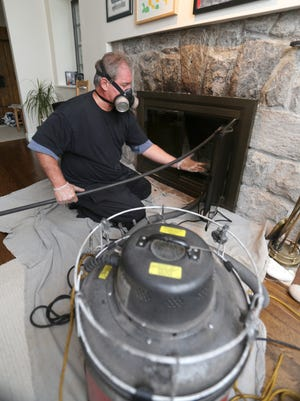 Bob Pelaccio, owner of the Mad Hatter Chimney Sweep from Montrose, cleans a fireplace flue at a home in Scarsdale, Sept. 30, 2015.