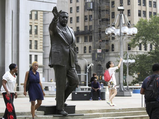 People walk by a statue of late Philadelphia Mayor Frank Rizzo outside the city's Municipal Services Building. The city will move the statue amid a national re-examination of the racially charged figures that are memorialized with statues.