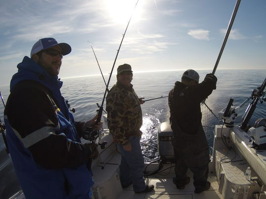 Andy Benoit, left, Bill Jackson and Bill Dunk land a lake trout aboard the Double Down.