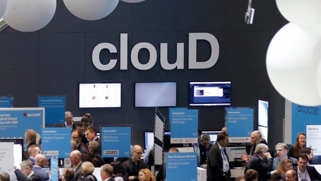Visitors walk under the word 'Cloud' at the IBM booth at the CeBIT computing trade fair in Hanover, Germany.