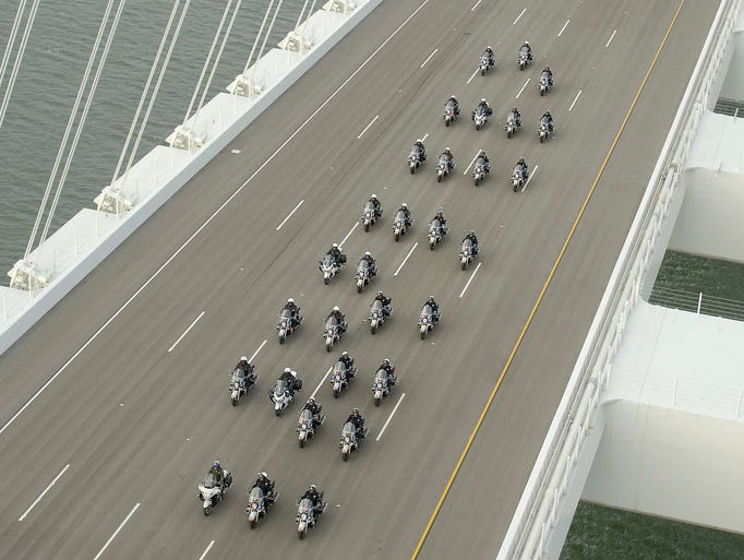 Police officers lead a procession of vehicles across the San Francisco-Oakland Bay Bridge to mark the opening of the east span on Sept. 2 in San Francisco. The new bridge was praised as a dramatic safety upgrade over the older structure.