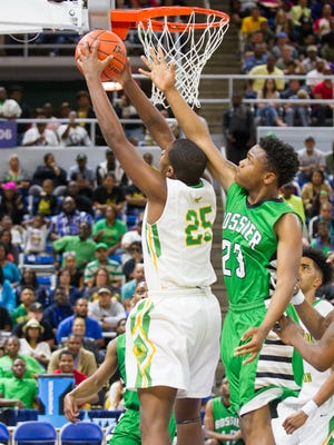 Washinton-Marion's Jaylon Ned (25) goes in against  Bossier's Tyrese English (23) for a shot during the Class 4A Allstate Sugar Bowl/LHSAA Boys' Top 28 Basketball Tournament at Burton Complex in Lake Charles, Louisiana on Saturday.