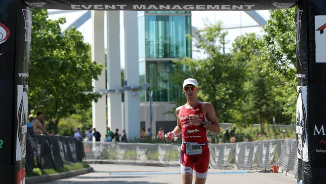 Tony White crosses the finish line to win the Music City Triathlon Sunday July 24, 2016.