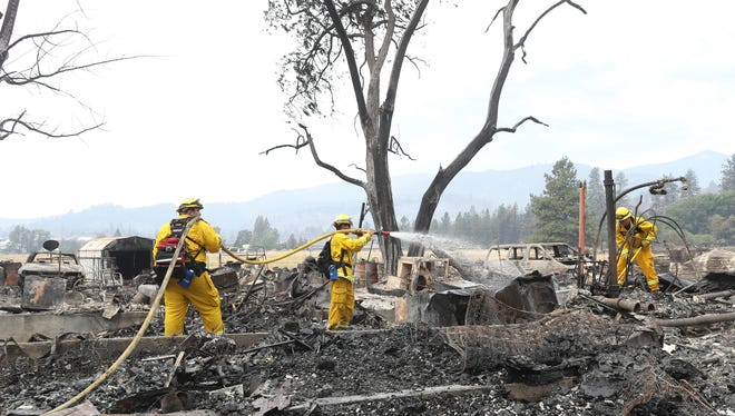 Lake Forest volunteer firefighters from left, Kyle Potter, Dylan Beck and Jerod Ellis work Friday, July 6, 2018 on putting out hot spots in an area burned down by the Klamathon Fire in Hornbrook.